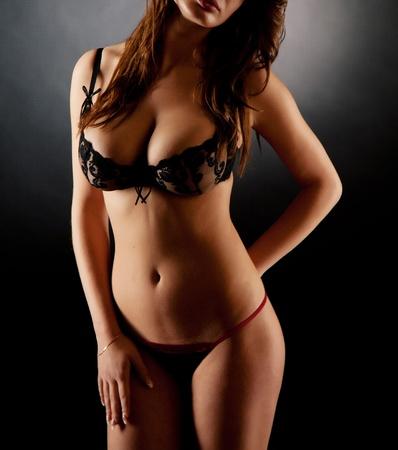 Girl in lingerie over dark background, studio isolated shot