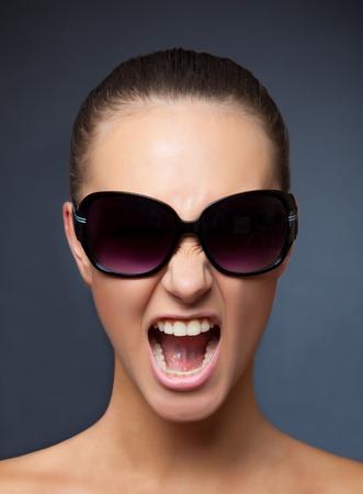 Schreeuwen meisje met zonnebril, verticale studio geïsoleerd schot Stockfoto