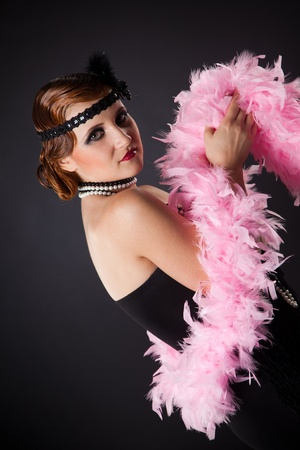 black boa: Retro-styled lady with pink necklet, studio isolated shot