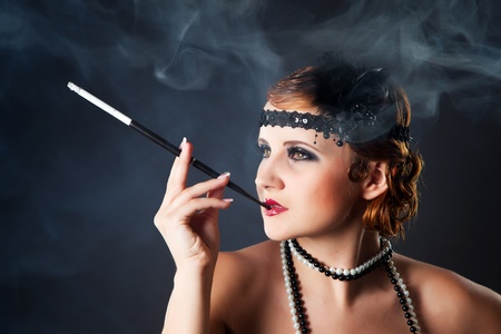 Smoking retro-styled sexy lady holding mouthpiece photo