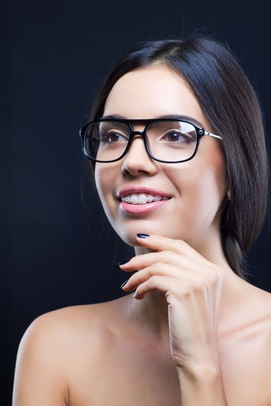Funny young girl with stylish glasses and teeth braces photo