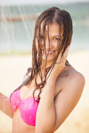 nice breast: Smiling girl taking outdoor shower after swimming
