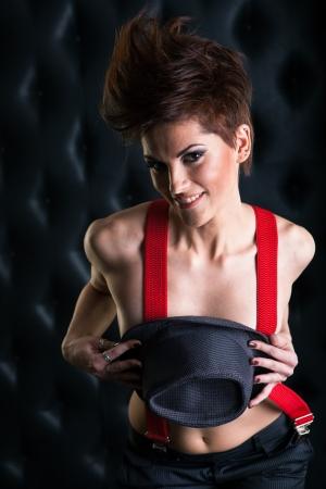 jeune fille adolescente nue: Crazy girl avec des bretelles rouges tenant un chapeau, studio shot