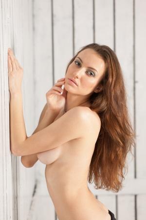 adult nudity:   brunette caucasian girl over white background