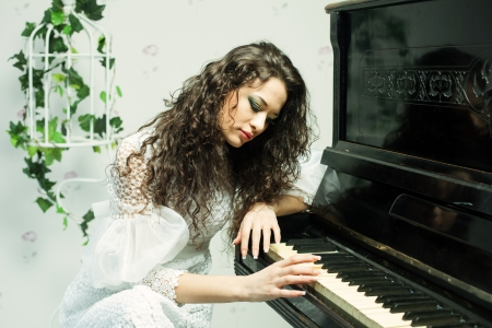 Romantic brunette girl playing piano, close up shot photo