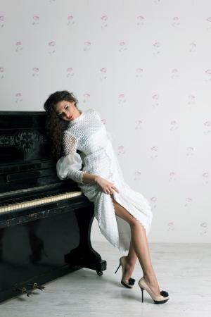 Girl and piano, studio shot photo