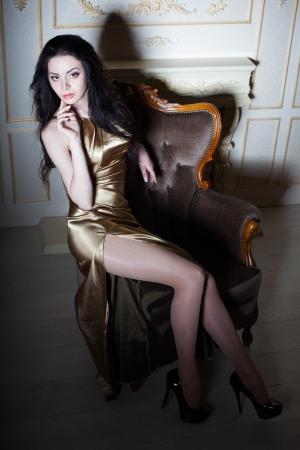 velvet dress: Sexy posing girl in golden dress, studio shot