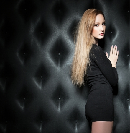 Blond girl over classic leather background, studio shot photo