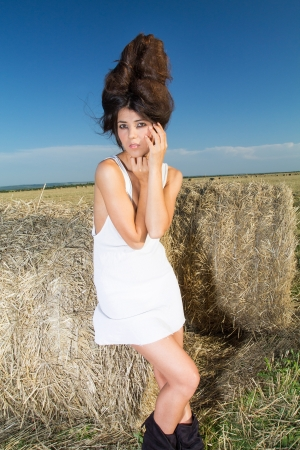 Fashionable image of a girl over farm background, portrait shot photo