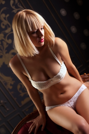 Sexy girl in white underwear sitting on the red sofa photo