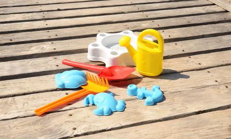 bailer: Toys set on a wooden pier, outdoor shoot