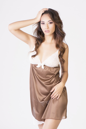 Vertical studio isolated shot of a sexy asian model in silky brown nightdress Banco de Imagens - 89409411