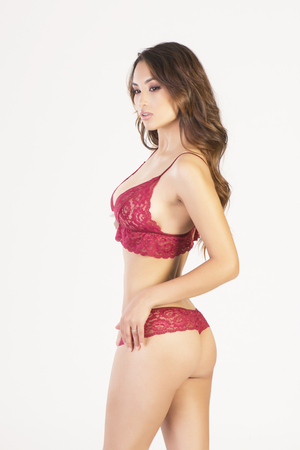 Sexy asian model posing in red lingerie set made from lace