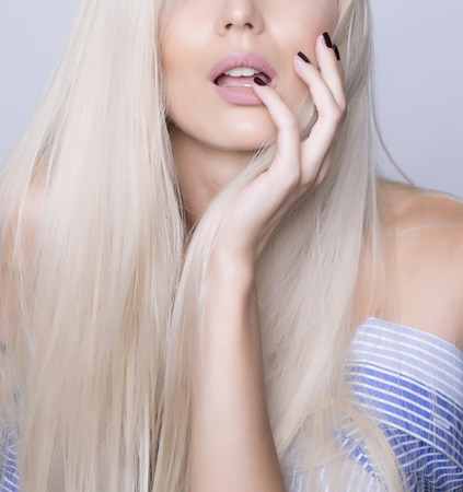 Sexy close up shot of a face, woman touching with fingers her teeths and tounge. Long platinum blonde hair.