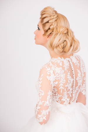 Nice and pure bridal look. Blonde young girl with elegant hairstyle looking up.