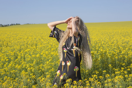 Summer heat. Girl posing in a yellow blooming field. Outdoor shot. Stock Photo
