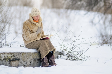 Woman sitting on a bench and reading a book in winter  Snow  photo