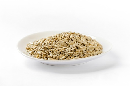 Sunflower seeds in a white plate, on white background Stock Photo - 18067636