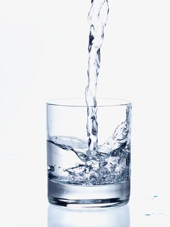 vaso con agua: Verter agua fresca en un vaso transparente Foto de archivo