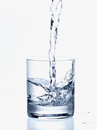 copa de agua: Verter agua fresca en un vaso transparente Foto de archivo