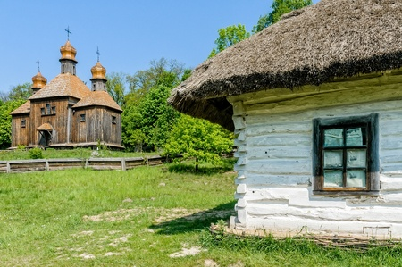 pirogovo: A typical ukrainian antique orthodox church, with a house detail  in the foreground  in Pirogovo near Kiev