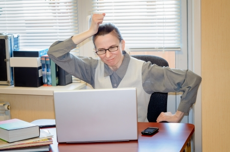 A fifty years old woman very angry with the modern technology of computer Stock Photo
