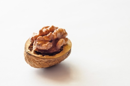 A close up of an open walnut on white background Stock Photo