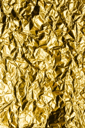Crumpled gold metal foil with ambient reflection