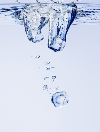 Ice cubes falling in clear water, with bubbles Stock Photo