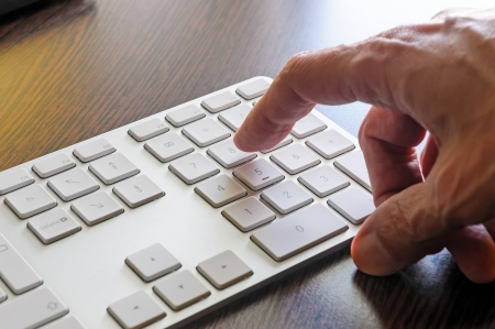 A senior man is using the numeric keyboard of his computer photo