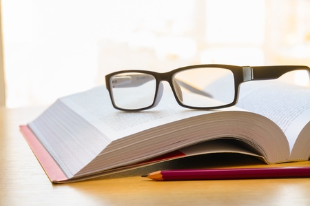 Reading a book using glasses, and taking some annotations with a pencil