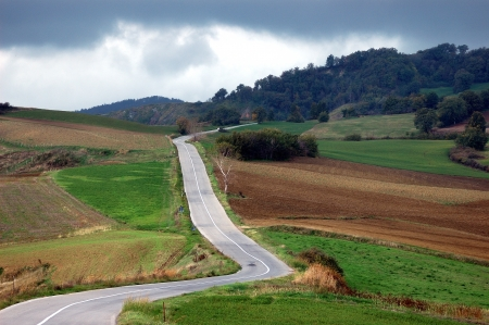 A long road in the Montefeltros hills, under a stormy sky Stock Photo
