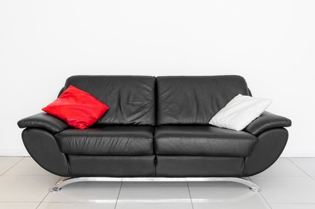 A black sofa with red and white cushion photo