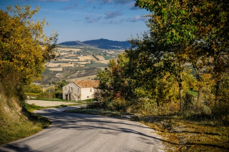 Driving downhill on a little road near Urbino in Italy. An antique house appears un a curve. Stock Photo