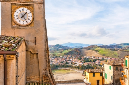 The clock tower of Sassocorvaro, vith a view of the little town of Mercatale in the background