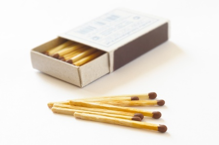 Open matchbox with some matches on a white table photo