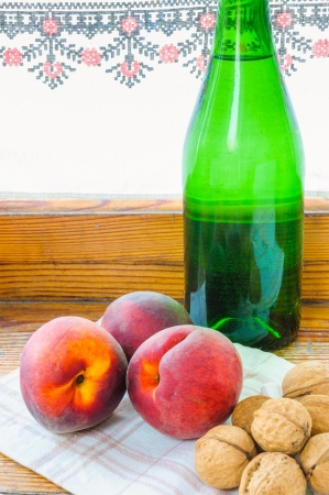 Three red peaches, a green glass bottle of wine and some walnuts, close to the window