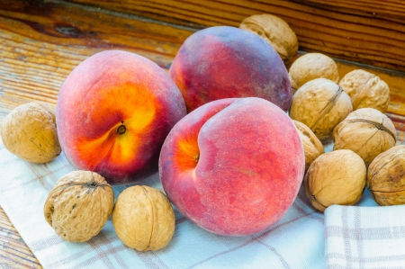 Three red peaches, and some walnuts close to the window