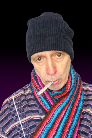 Senior man with the flu and temperature, wearing a cap and a woolen scarf photo