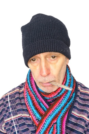 Senior man with the flu and temperature, wearing a cap and a woolen scarf