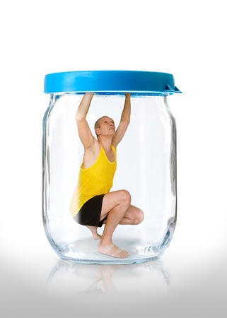 alienation: A man trapped in a glass jar  with the closed blue color lid Stock Photo