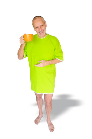 A happy man in green nightdress, smiling and hanging an orange cup of coffee