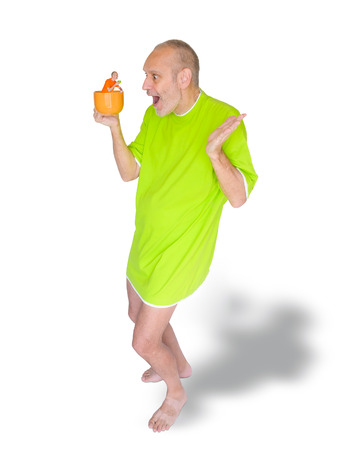 nightdress: A man in green nightdress surprised to see himself in his coffee cup Stock Photo
