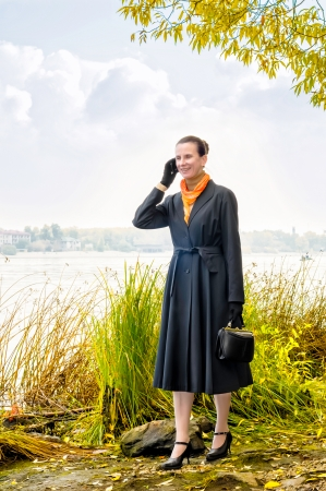 Elegant senior business woman with a mobile phone, a bag and an orange scarf, walking along the river, under the trees in autumn photo
