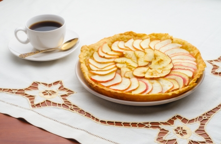 A tasty golden homemade apple tart and a cup of black coffee on an embroidered tablecloth photo