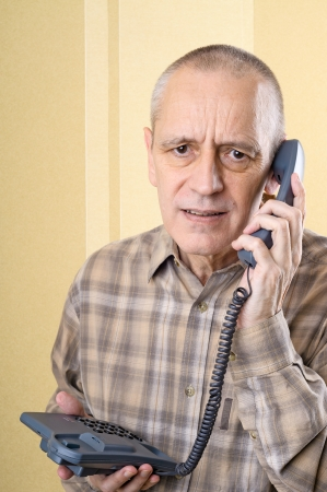 solicitous: Upset man having bad news and holding a phone in hand