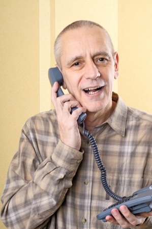 neighbourly: Handsome man speaking softly with a friend on the phone Stock Photo