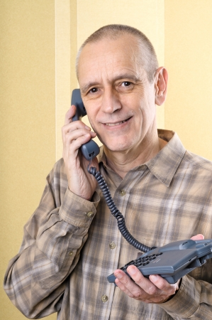 neighbourly: Bright man smiling while speaking on phone