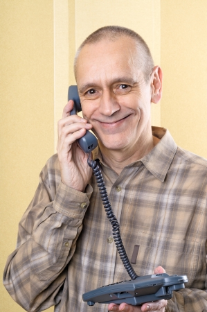neighbourly: Happy smiling man speaking on phone at home