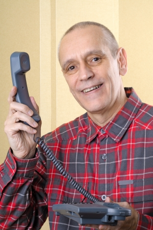 neighborly: A senior man giving the phone handset to somebody else - There is a call for you